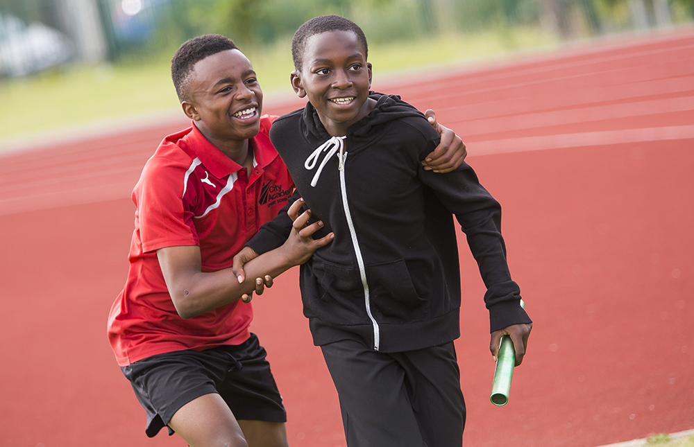 Two young boys running a relay race