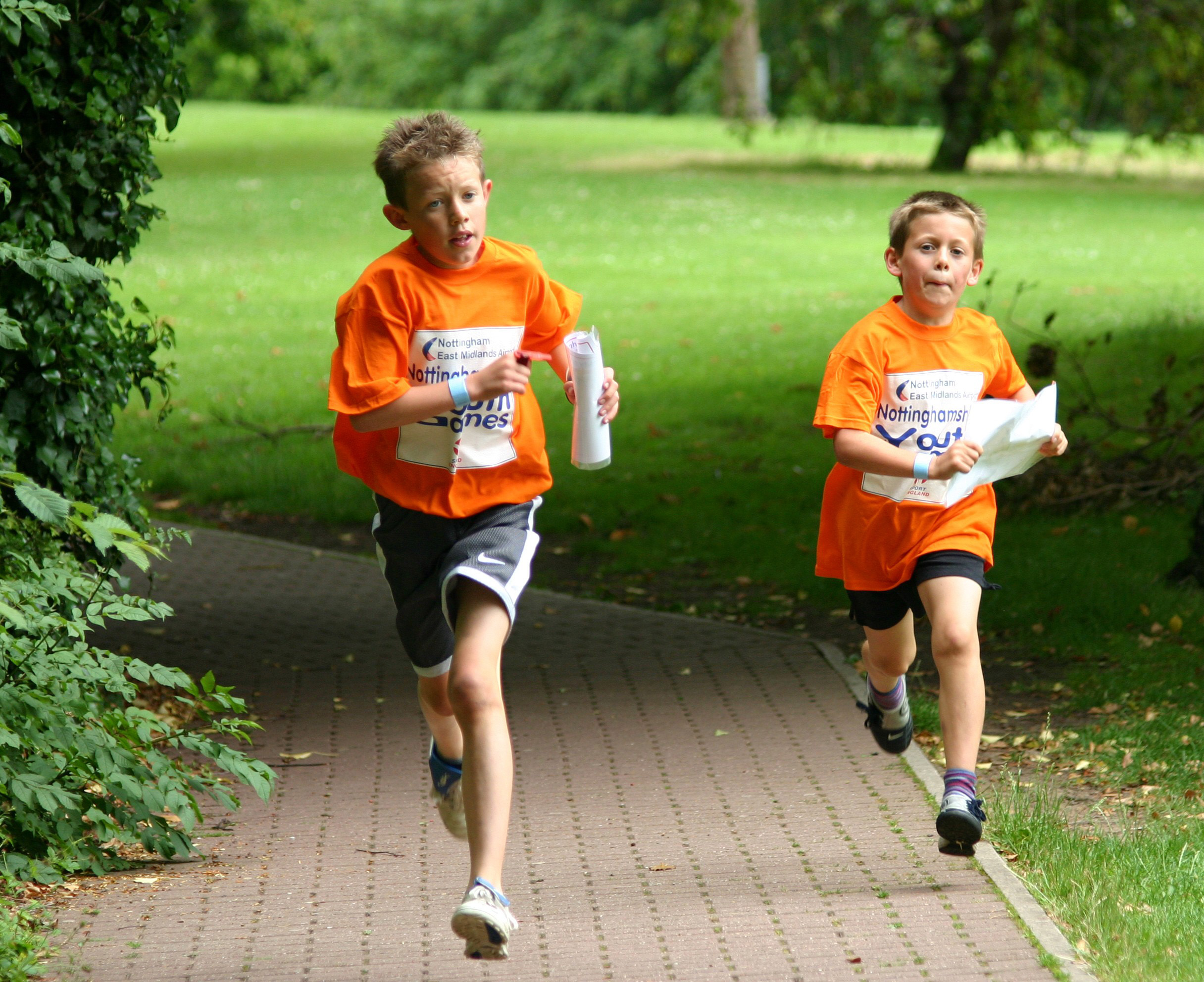 Two primary school aged boys running along a path