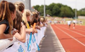 A group of children watching at the side of a track whilst a 100m race is taking place.