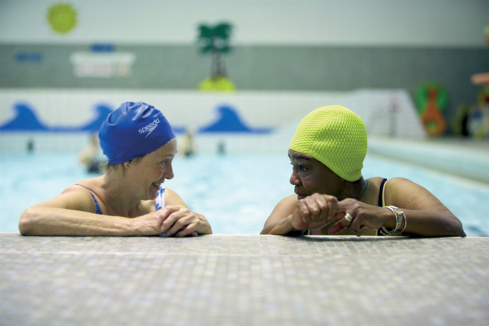 Two women chatting at the end of a Swimming Pool. Sport England Funding Update