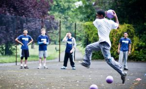A teenage boy playing handball in his school play ground.