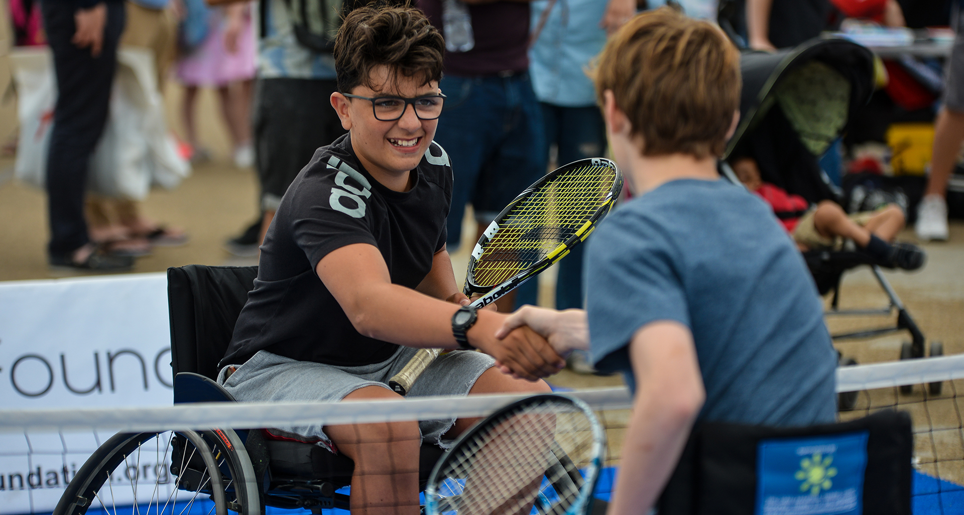 Two boys shaking hands after playing wheelchair Tennis. Partners